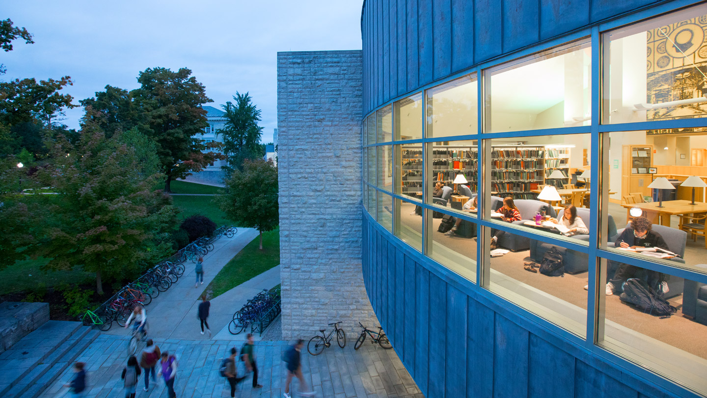 Exterior view of Middlebury's Davis Family Library at dusk, with a view through the lighted windows to students inside studying.