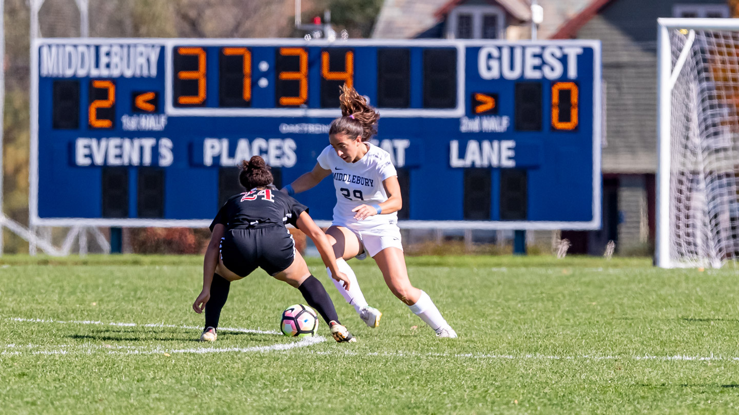 A close up of two women playing in a varsity soccer game on the Middlebury field.