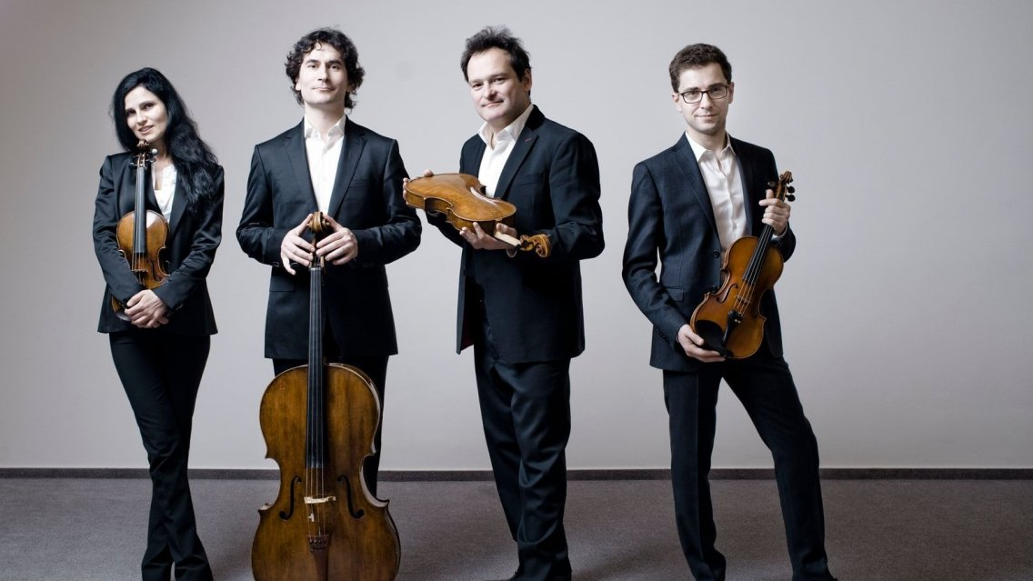 one female and three male musicians, standing, holding string quartet instruments