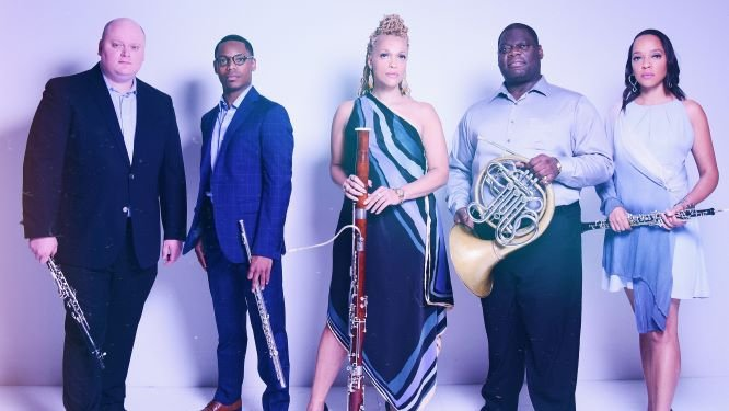 Quintet of diverse musicians holding wind instruments