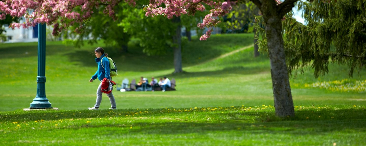 A student walks across the grassy campus quad on an early spring day.