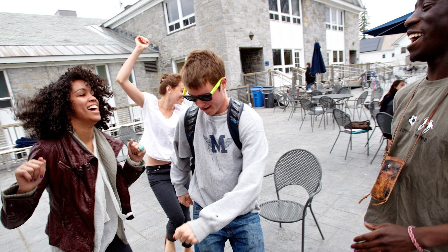 Four Middlebury students dancing and talking on an outdoor dining patio.