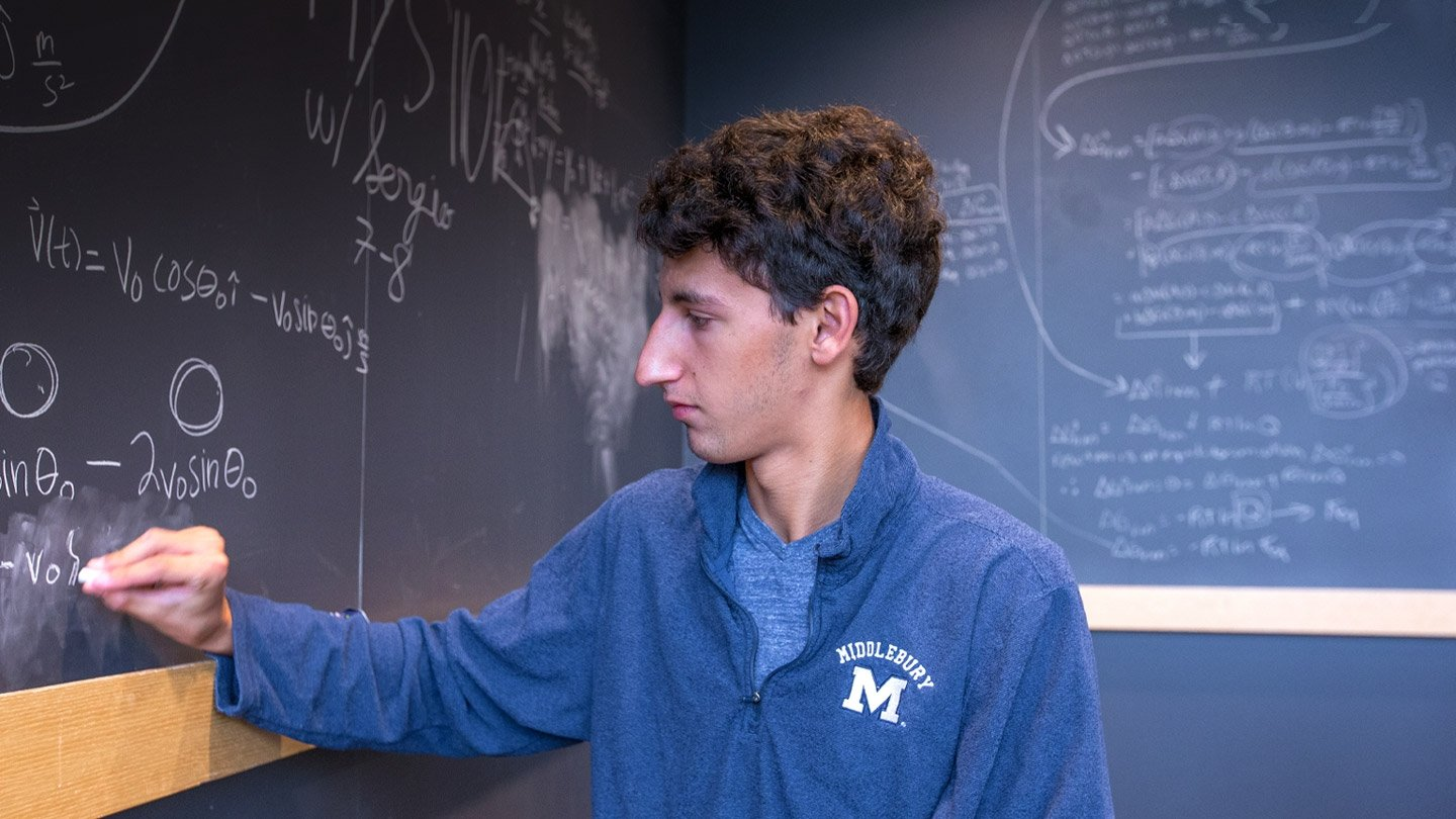 A Middlebury student writing on a chalkboard.