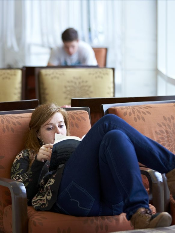 A student reads curled up in a comfortable chair at Middlebury's Davis Family Library.