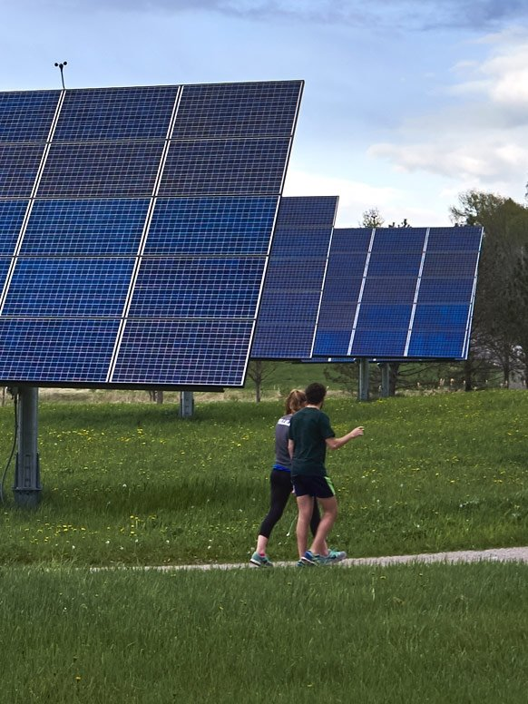 Student run on a trail around Middlebury that passes through the college's solar array.