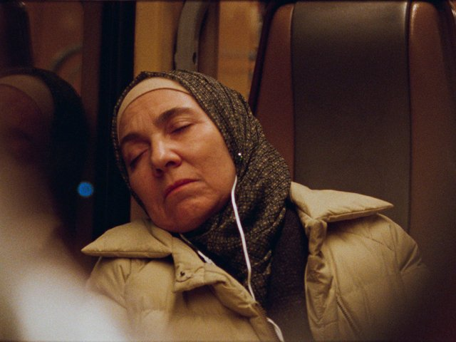 A middle aged woman asleep on a bus