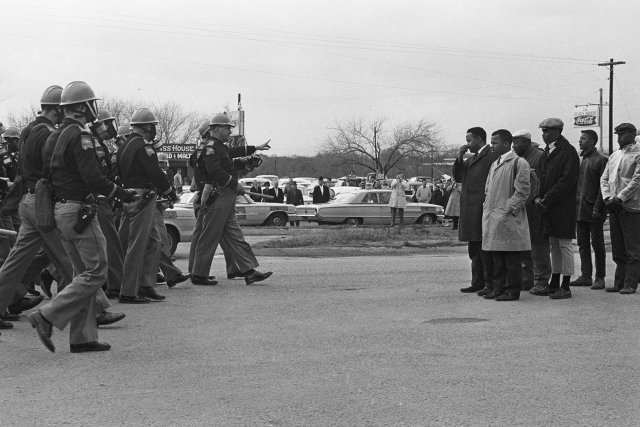a black and white photo of police approaching civil rights protestors on the Edmund Pettus bridge