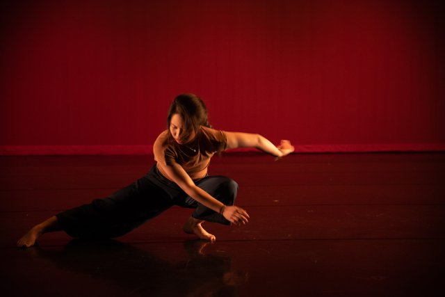 a dancer lunges down low in front of a red background