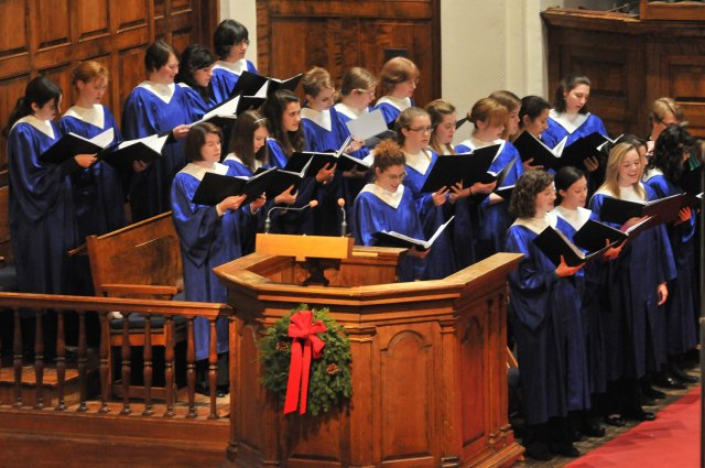 A group of choir singers in blue robes, in Mead Chapel, with a holiday wreath