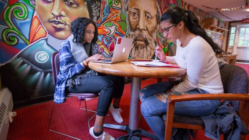 Two woman study beside a full sized colorful wall mural in Middlebury's Anderson Freeman Resource Center,