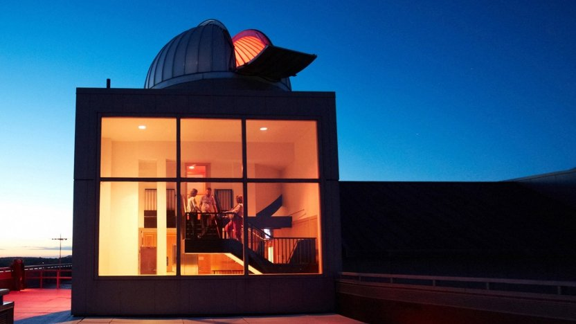 Nighttime view of Middlebury's Mittelman Observatory lit up from inside.