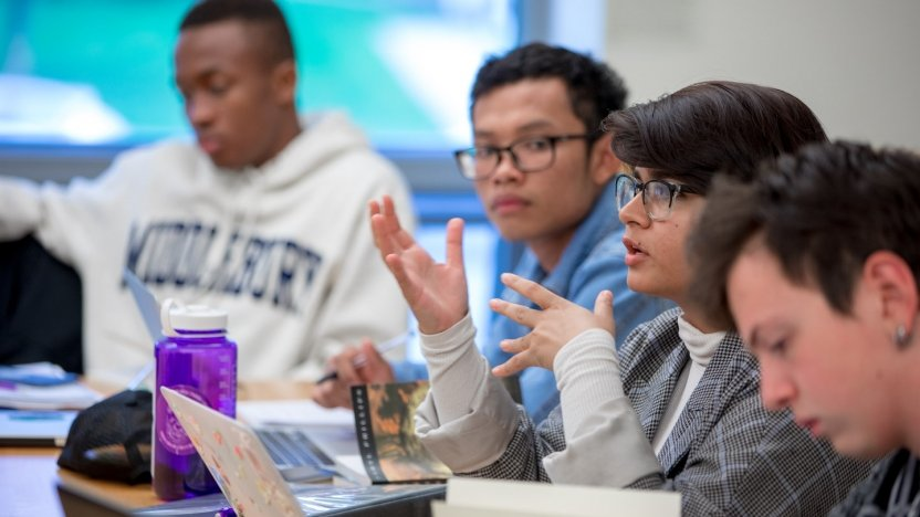 A close-up of several students in a classroom discussion.