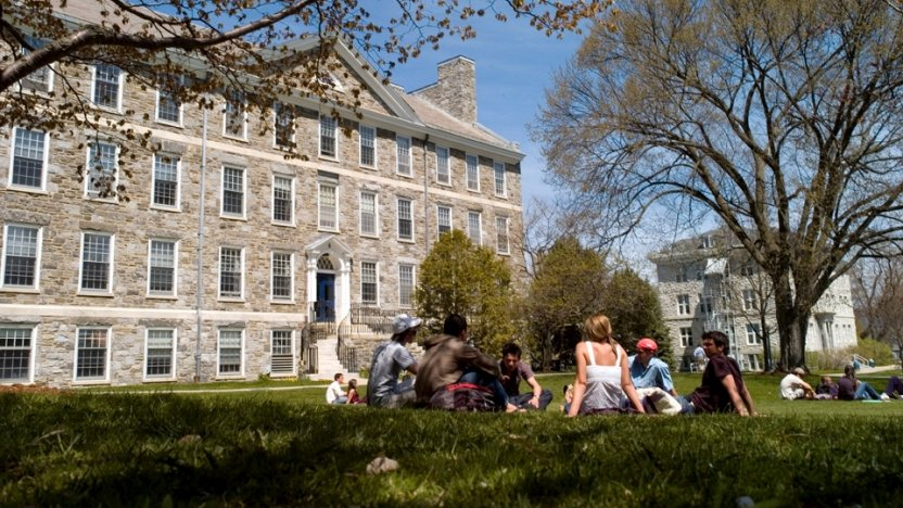Students sitting in a circle outside a building at Middlebury College