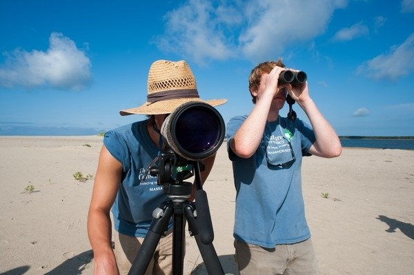 Students looking through binoculars while doing an internship on the ocean.