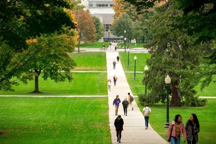 Students walking on a campus path on a Fall day