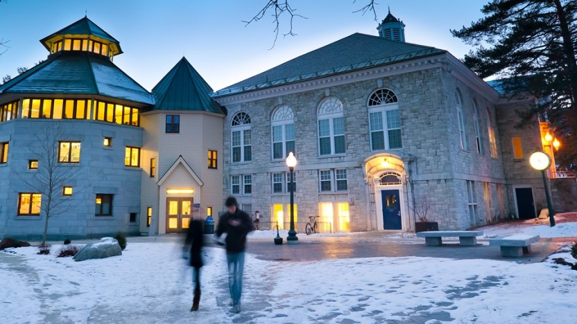 Two students catch up outside McCullough Student Center at dusk in early winter.