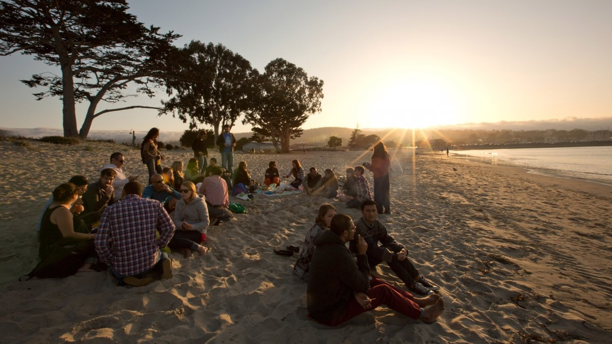 Students gather on the beach during sunset