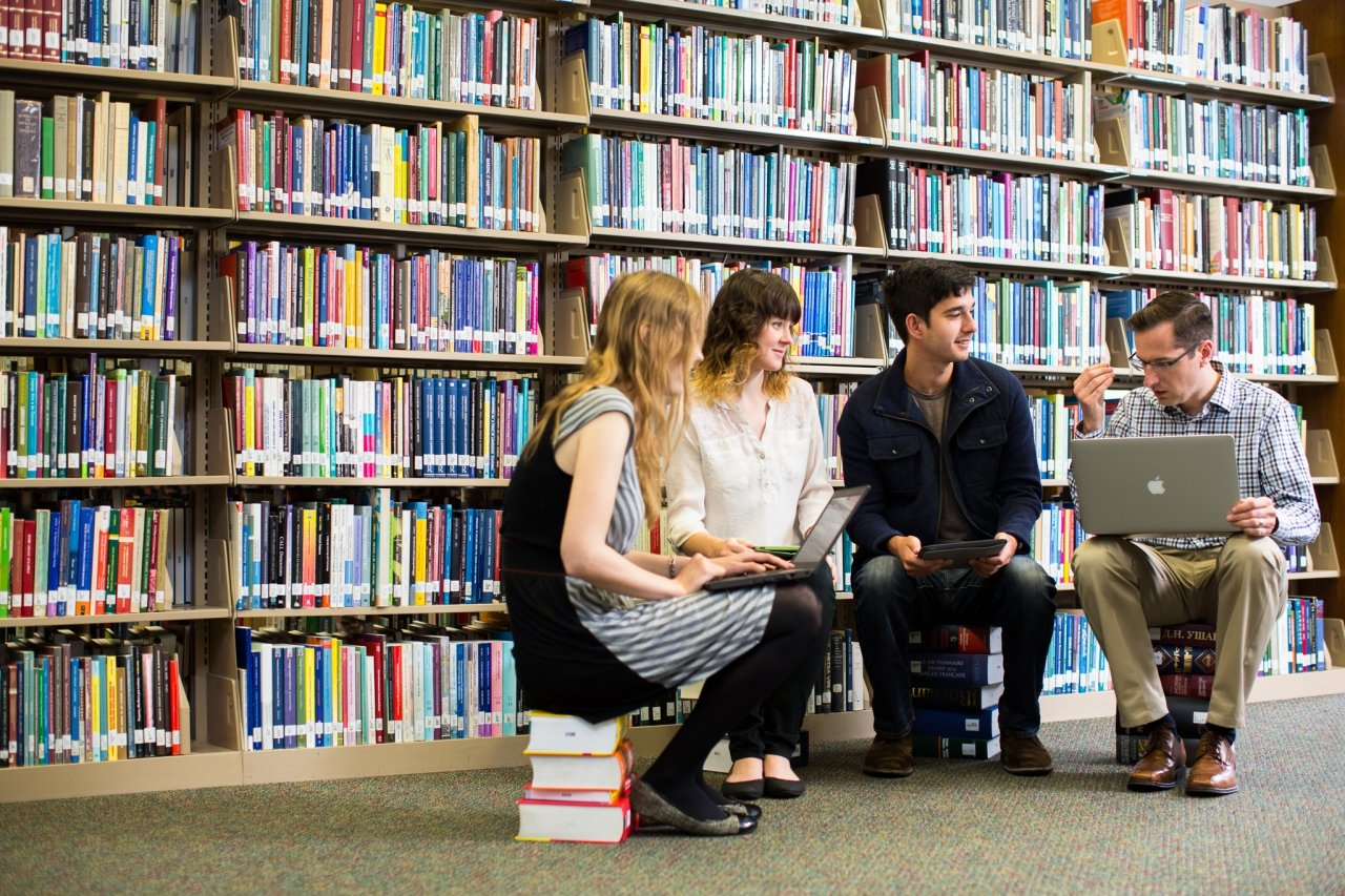 Max Troyer Sitting on Books with Students