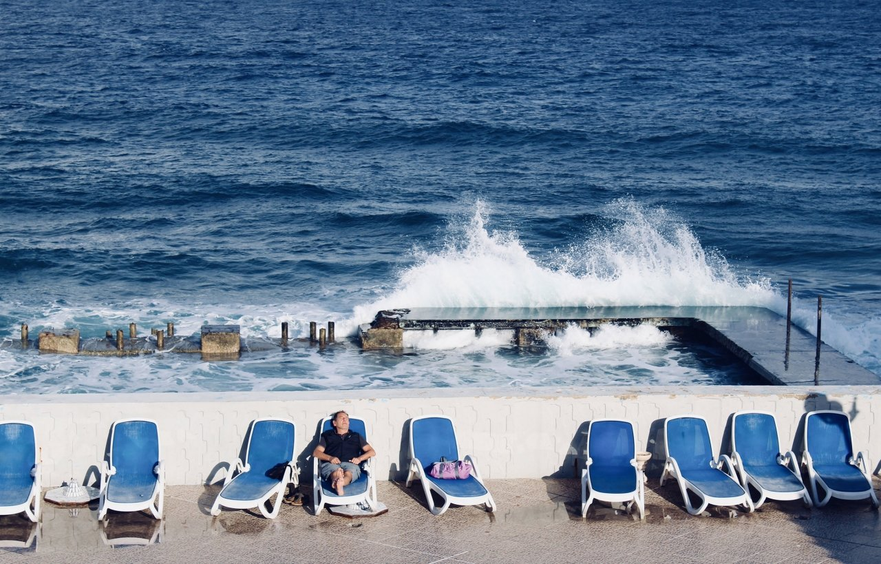 Man Relaxing in Lawn Chair with Waves Crashing Behind Ominously