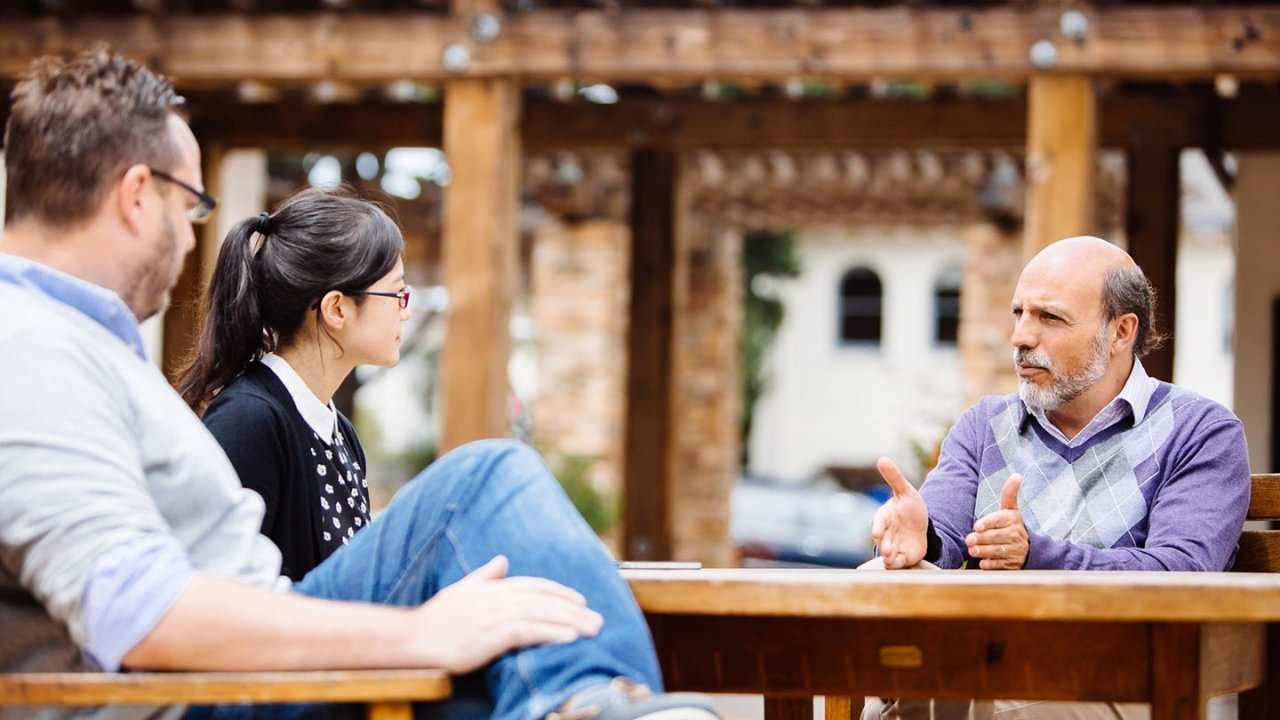 Professor Arrocha in discussion with two students outside at a table.