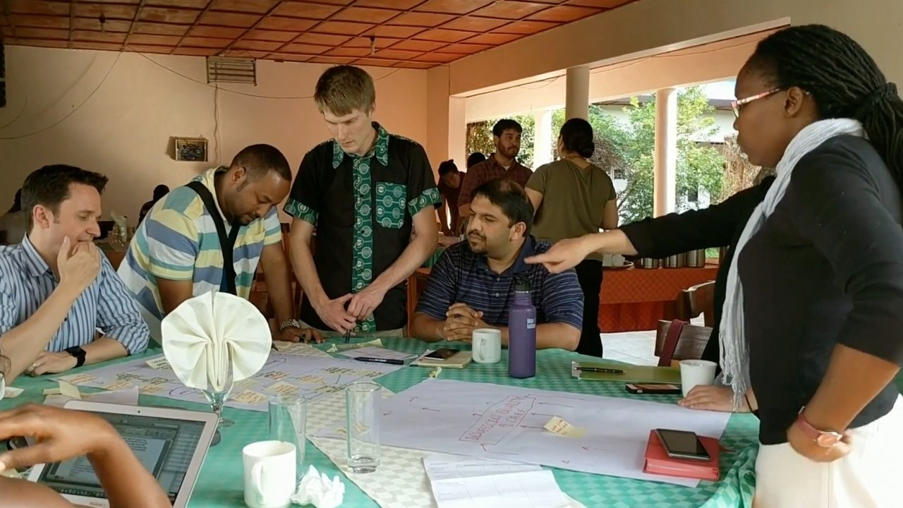 Team of DPMI participants around a table discussing a project