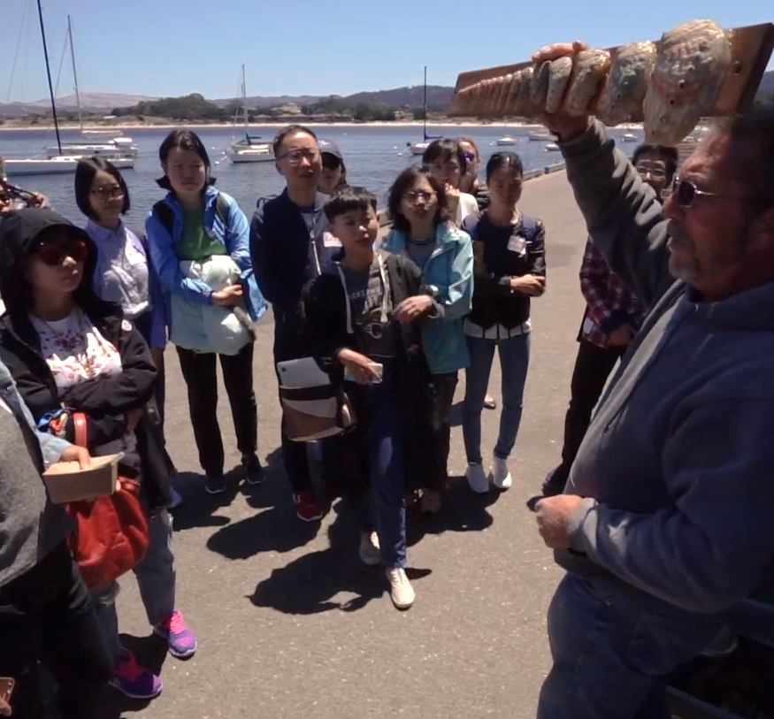 Man holding up abalone shells to group of people in front of harbor.