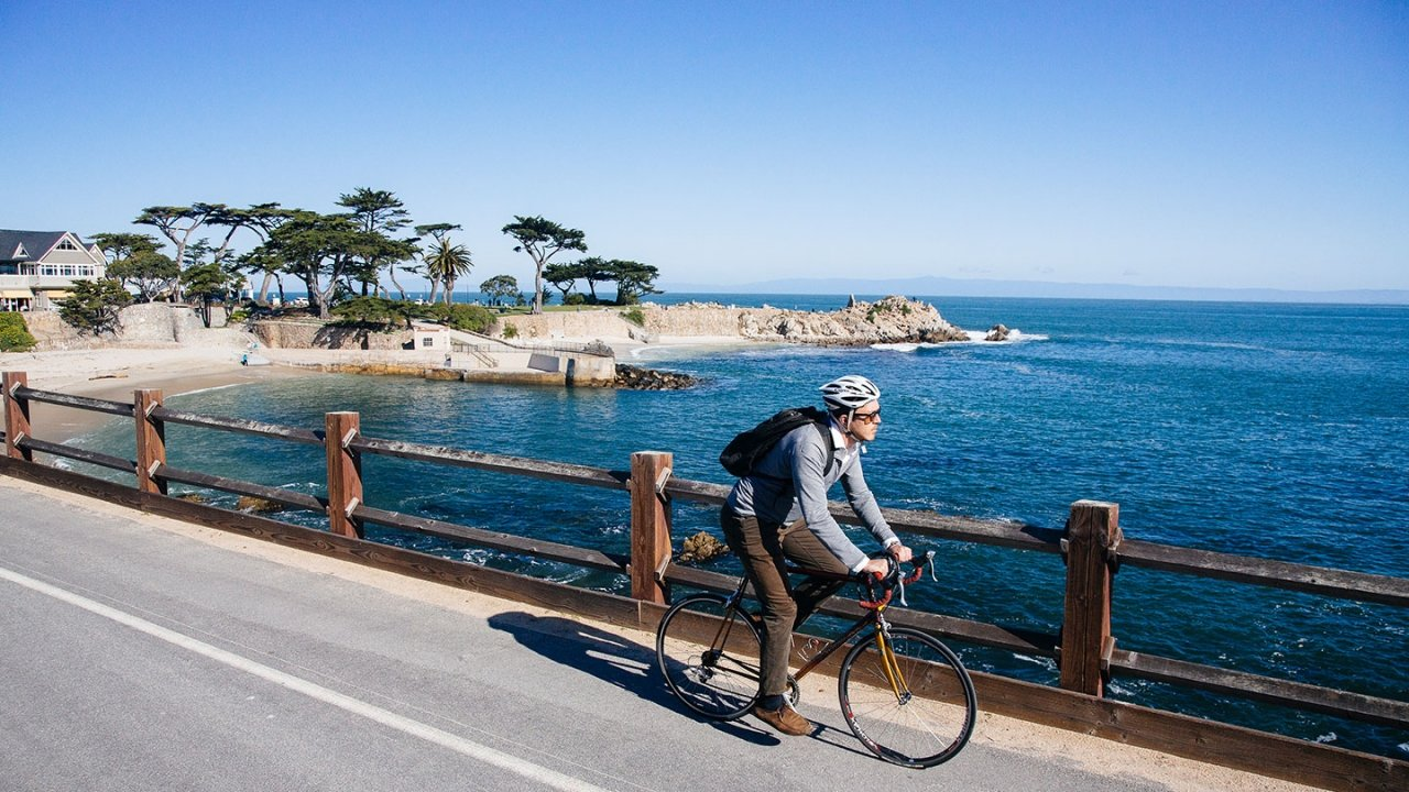 Student riding bicycle along the Monterey coast
