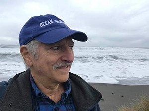 David Helvarg, Director of Blue Frontier, older white dude with blue cap on, shown in front of ocean in Humbolt, CA