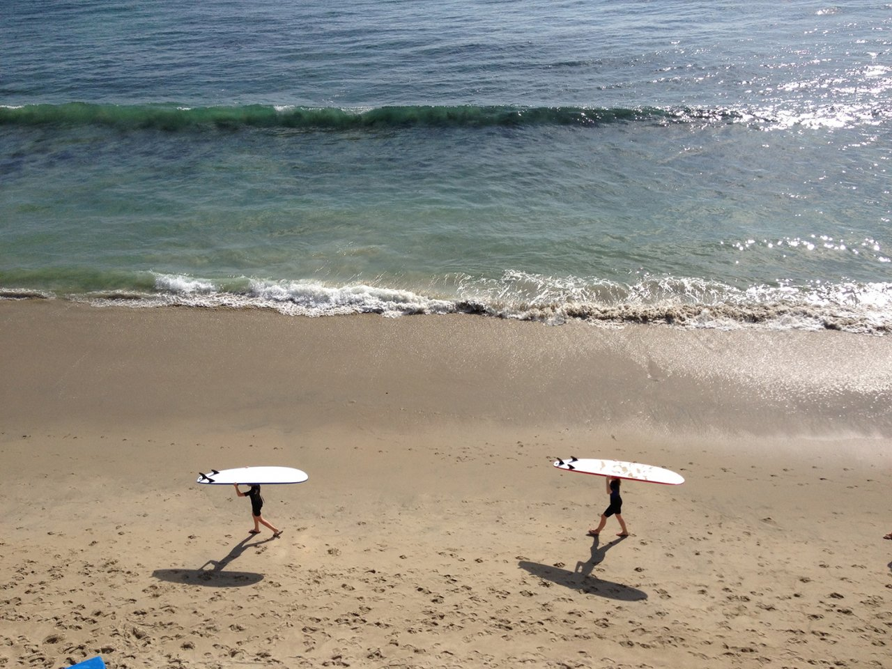 Two ladies walking on beach with surfboards balanced on their heads