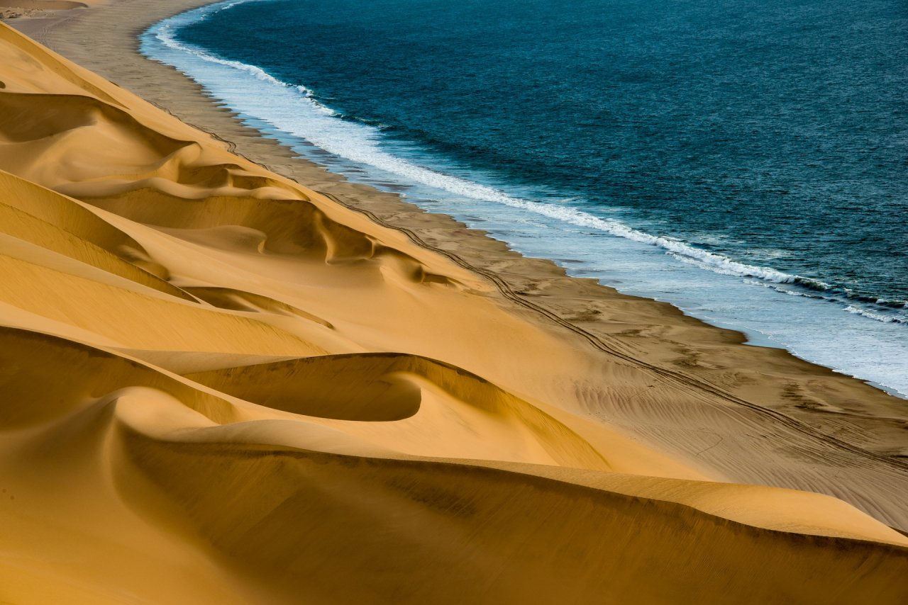 Striking image of golden, swirling sand dunes dropping off to blue ocean