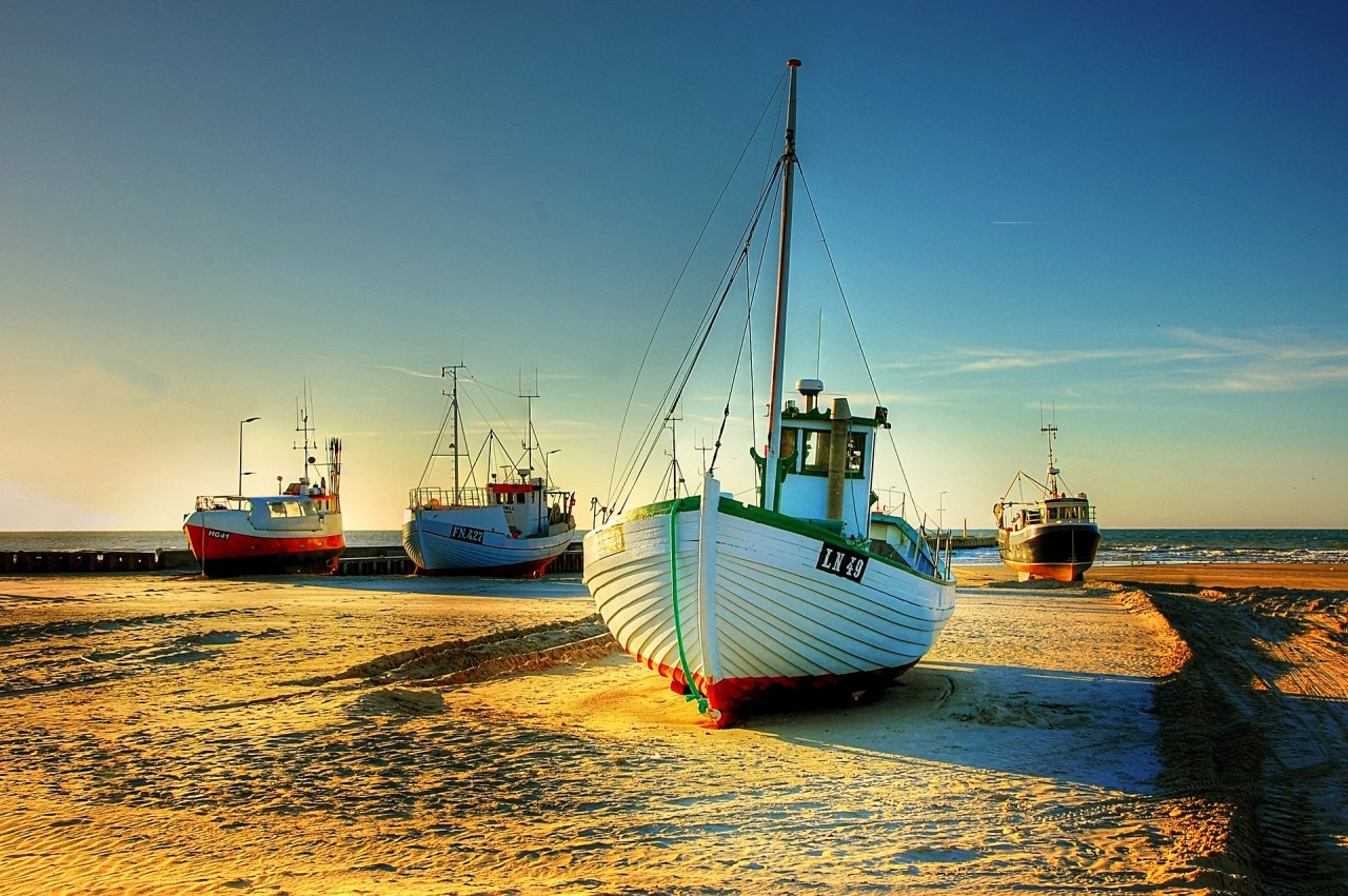 Fishing Boats on land with sky and sea behind