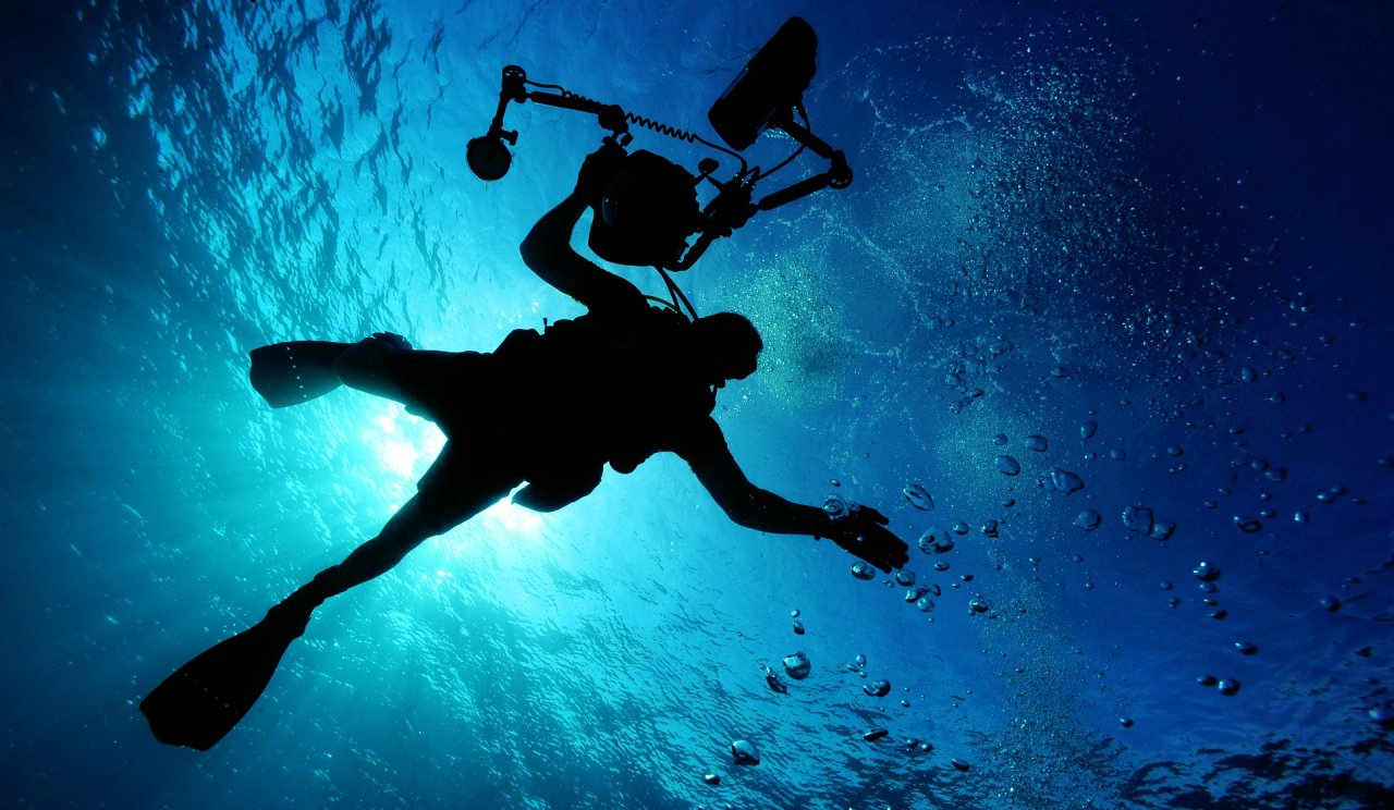 Scuba diver in blue ocean with light from behind slash above
