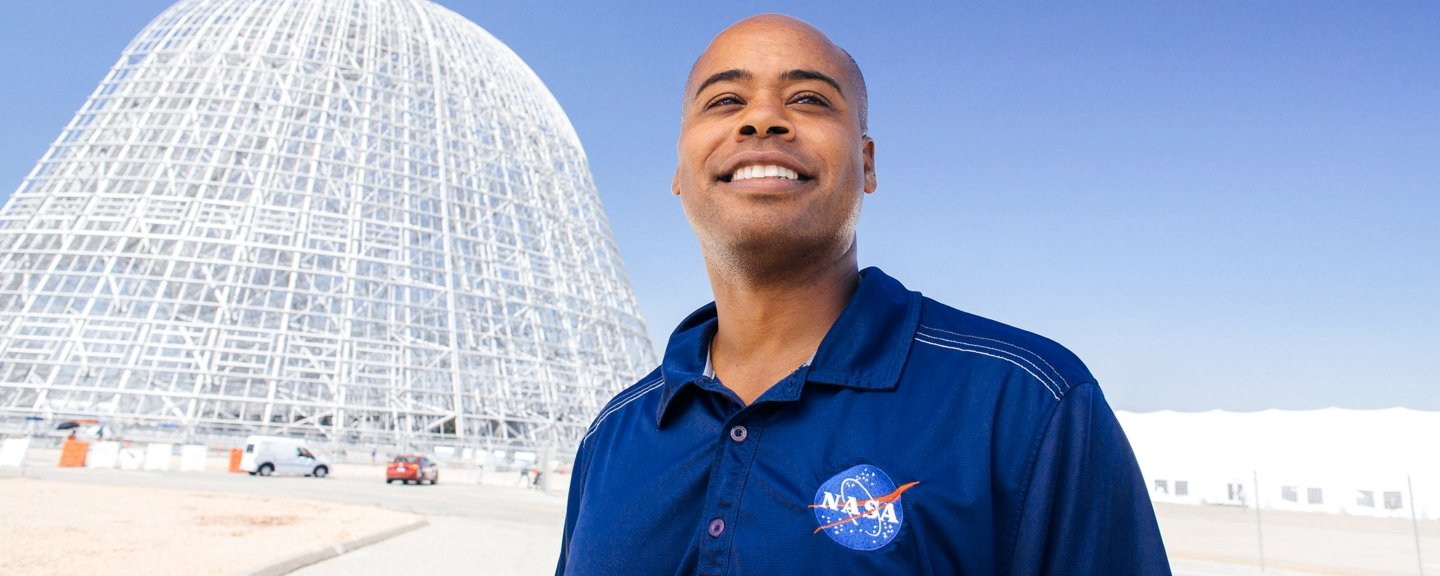Profile photo of an alumnus standing proudly where he works at NASA.