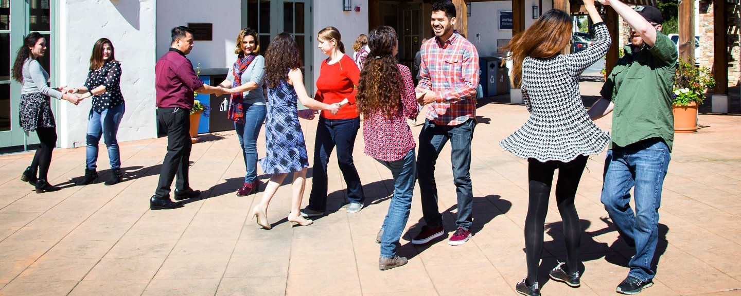 Students participate in an outdoor square dance on the campus patio.