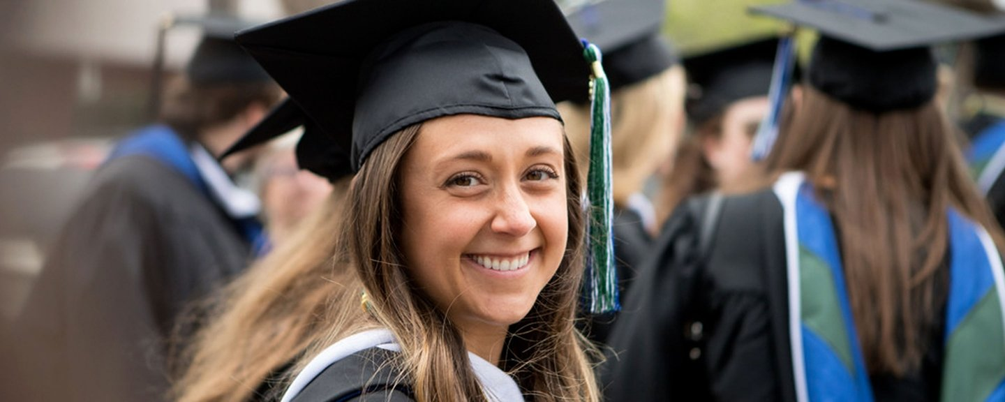 A female graduate smiles at the camera while at commencement.