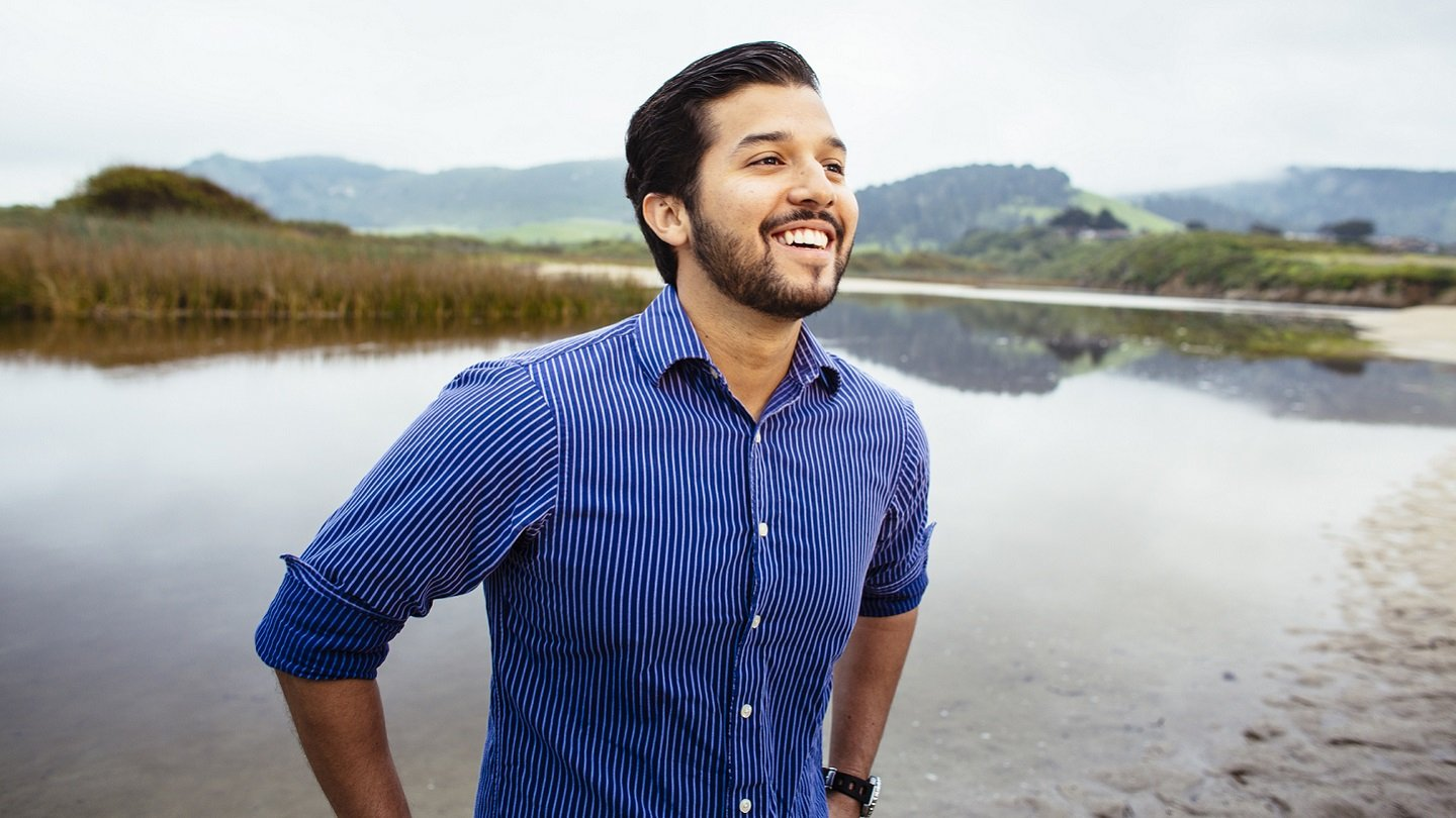 William Franco, international environmental policy alumnus, smiling and standing outside by a marsh in Monterey