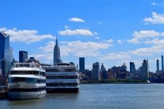 Manhattan with Cruise Ship, blue sky, blue water, two large cruise ships sit against city skyline