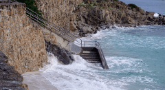 Ocean splashing and covering steps leading to the beach