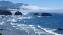 Sunny, waves, large rocks, and fog lifting in front of a mountain