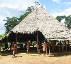 Indigenous people of the Bora community gathers together in a straw hut in Iquitos, Peru