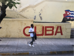 "African American man walking on the street in front of a mural on a wall which reads ""Cuba"" in red letters"