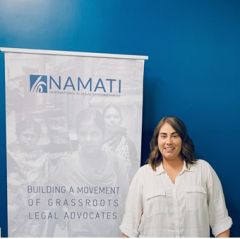 A girl with brown hair in a white shirt standing in front of a sign for Namati with a blue wall as the background.