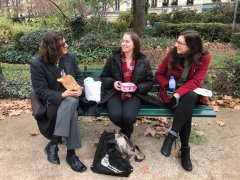 Three people are talking in a park in Paris while sitting on a bench eating food.