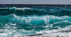 ocean waves of various colors of blue and turquiose, crashing gently