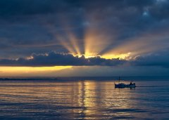 Fisherman at Sunrise on a broad sea, big sky, light rays from the sun
