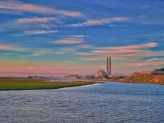 Image of Moss Landing (now retired) power plant at Elkhorn Slough--a big sky above with pastel colors, big water below as the slough spread out