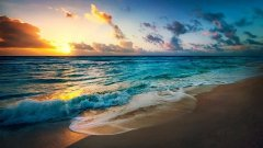 Orange sunset over turquoise blue water at a broad sandy beach