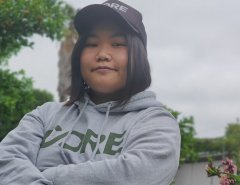 Emily Hoang looking at the camera with her arms folded, wearing a CORE hoodie and cap