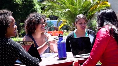 Students around an outdoor table discuss a class project.