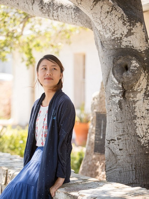 Carol Lin, graduate of the MA in International Education Management, sitting in front of a tree